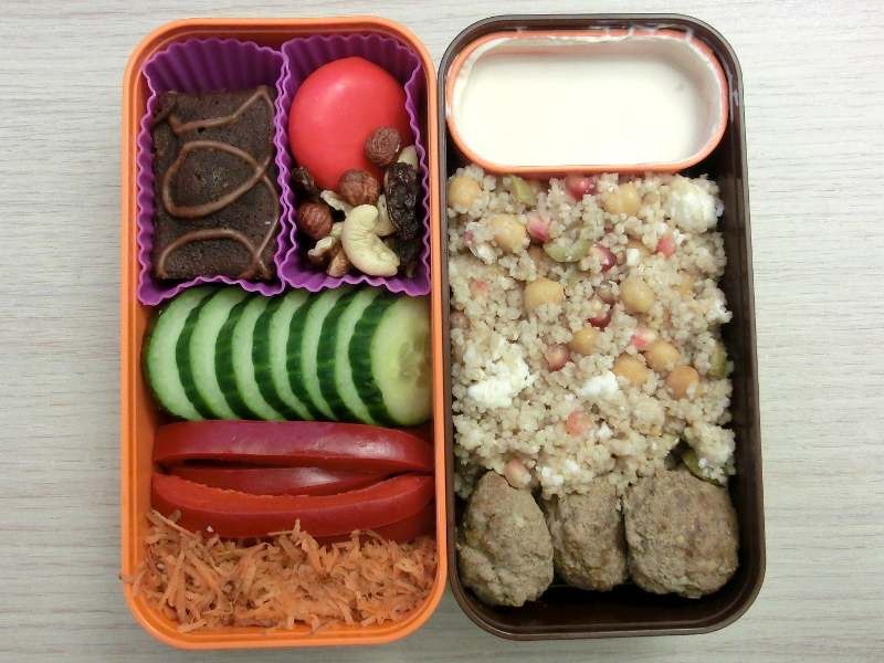 Bento Box gefüllt mit Cous Cous Salat, Lammhackbällchen, Joghurt-Dipp, Brownie, Babybel, Studentenfutter, Gurke, Paprika, Möhren