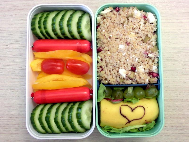 Bento Box gefüllt mit Paprika, Wurst, Gurke, Cous Cous, Weintrauben, Banane