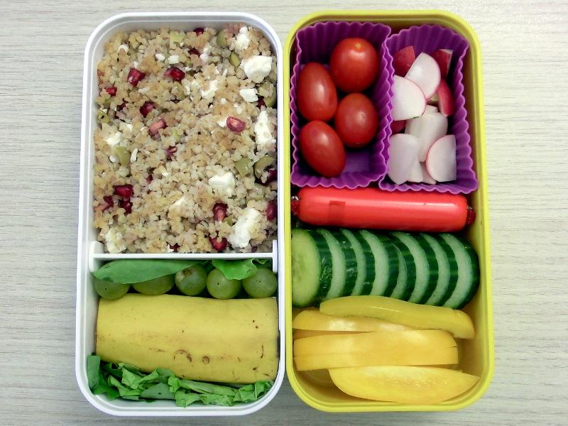 Bento Box gefüllt mit Cous Cous, Weintrauben, Banane, Gurke, Paprika, Fleischwurst, Tomaten, Radieschen