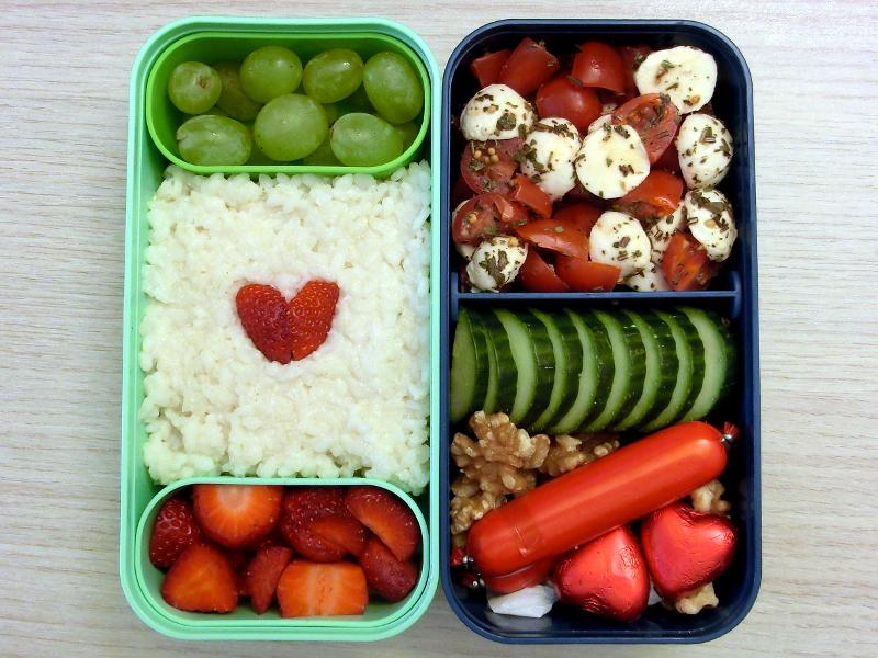 Bento Box gefüllt mit Gurke, Tomaten, Morzarella, Fleischwurst, Walnüsse, Schokolade, Milchreis, Erdbeeren, Weintrauben