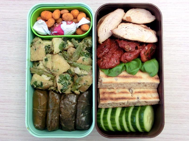 Bento Box gefüllt mit Kartoffelsalat, Gefüllte Weinblätter, Erdnüsse, Schokolade, Hähnchenbrustfilet, Getrocknete Tomaten, Brot, Gurke