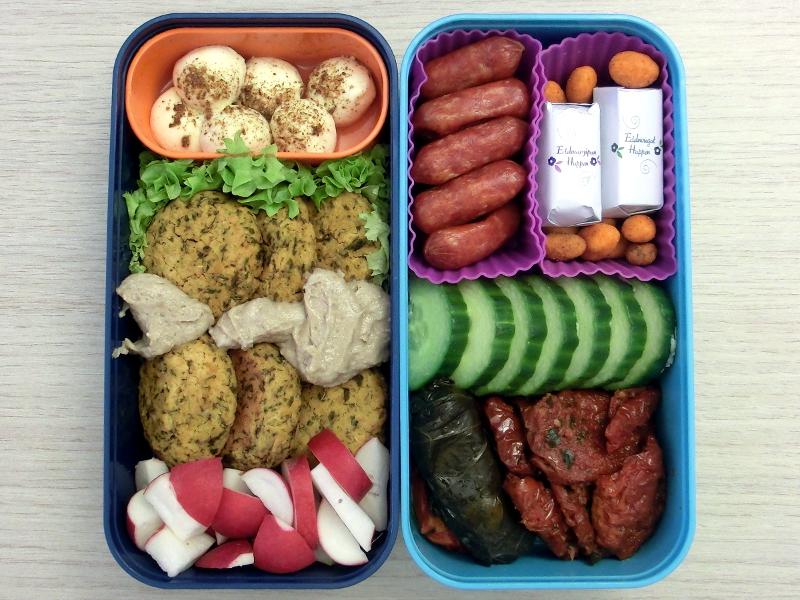 Bento Box gefüllt mit Radieschen, Falafel, Mozzarella, Cabanossi, Erdnüsse, Schokolade, Gurke, Getrocknete Tomaten, Gefüllte Weinblätter