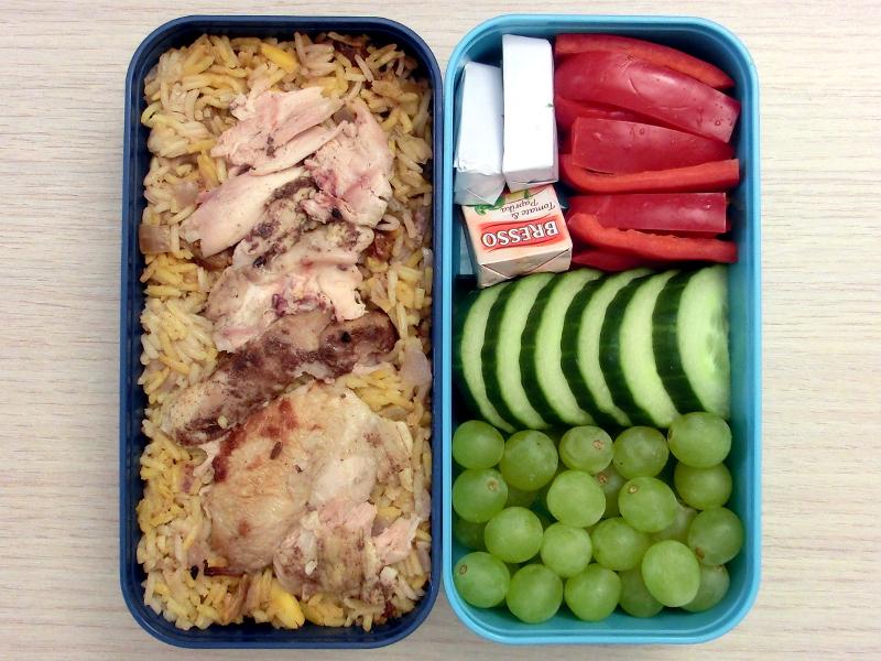 Bento Box gefüllt mit Pilaw, Hühnchen, Käse, Paprika, Gurke, Weintrauben