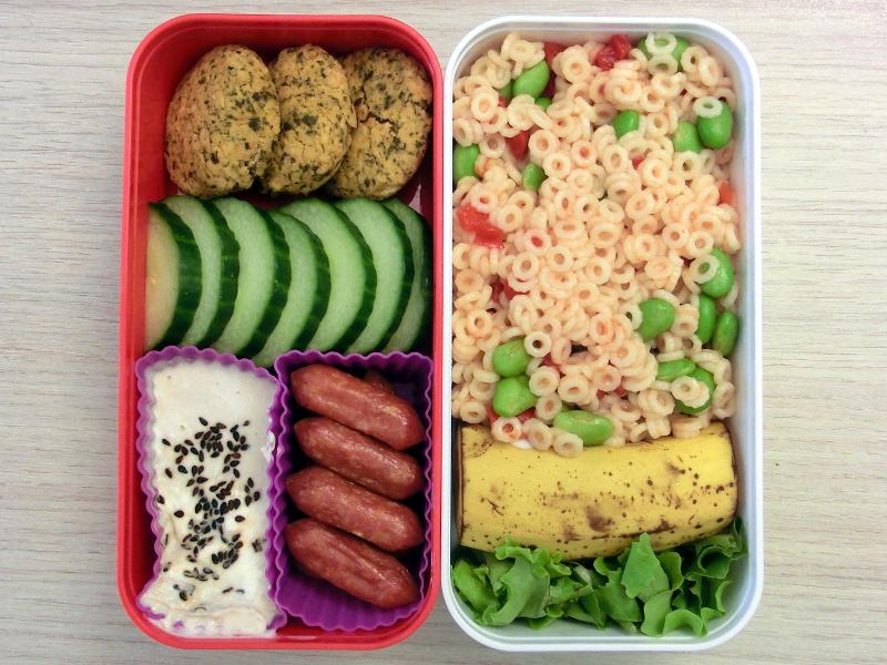 Bento Box gefüllt mit Nudeln, Banane, Falafel, Gurke, Cabanossi, Dipp