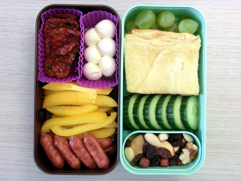 Bento Box gefüllt mit Getrocknete Tomaten, Mozarella, Paprika, Cabanossi, Weintrauben, Zitronenzupfbrot, Gurke, Studentenfutter