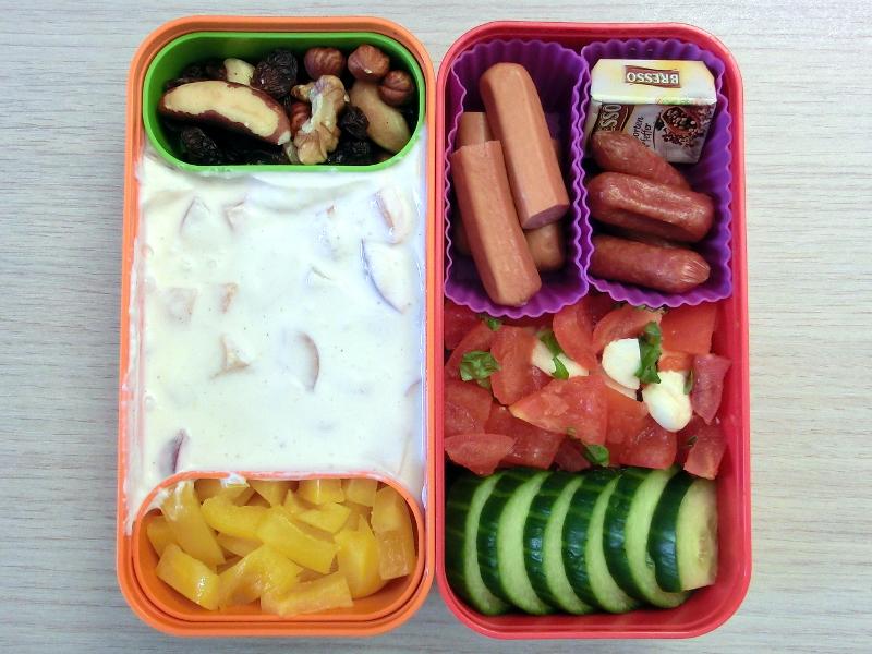 Bento Box gefüllt mit Würstchen, Cabanossi, Käse, Tomaten, Morzarella, Gurke, Fruchquark, Paprika, Studentenfutter