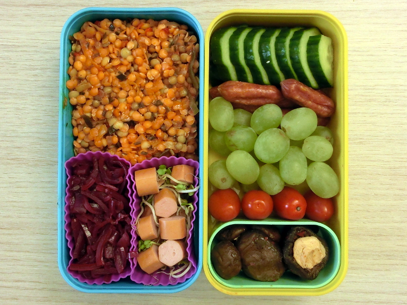 Bento Box gefüllt mit Linsen, Pickled Onions, Wurstsalat, Gurke, Cabanossi, Weintrauben, Tomaten, Champignons