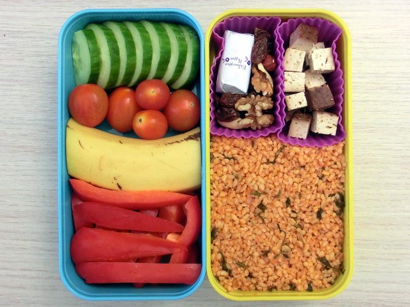 Bento Box gefüllt mit Gurke, Banane, Tomaten, Paprika, Cous Cous, Tofu, Studentenfutter, Schokolade