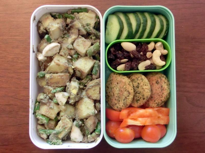 Bento Box gefüllt mit Kartoffelsalat, Tomaten, Paprika, Falafel, Studentenfutter, Gurke