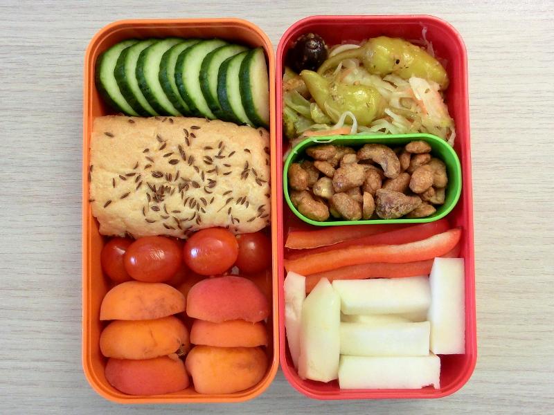 Bento Box gefüllt mit Kohlrabi, Paprika, Erdnüsse, Salat, Gorke, Brötchen, Tomaten, Aprikosen