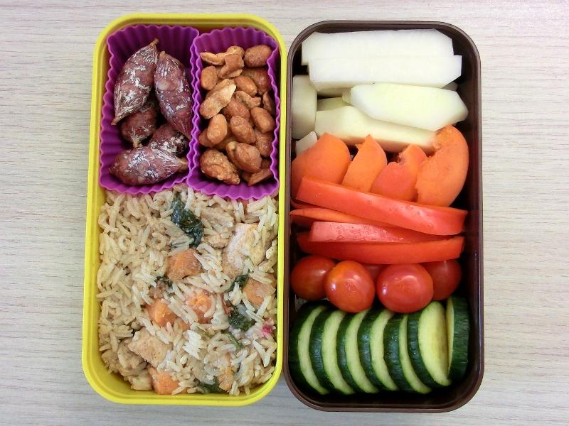 Bento Box gefüllt mit Salami, Erdnüsse, Hähnchen mit Reis, Kohlrabi, Aprikosen, Paprika, Tomaten, Gurke