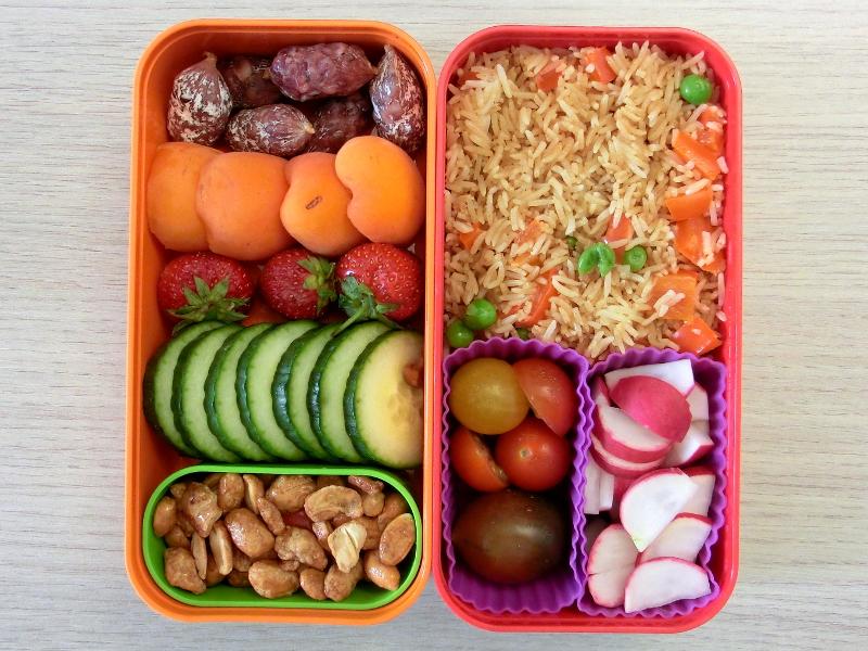Bento Box gefüllt mit Reis, Tomaten, Radieschen, Salami, Aprikosen, Erdbeeren, Gurke, Erdnüsse
