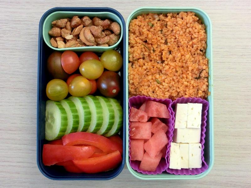 Bento Box gefüllt mit Cous cous, Schafskäse, Wassermelone, Erdnüsse, Tomaten, Gurke, Paprika