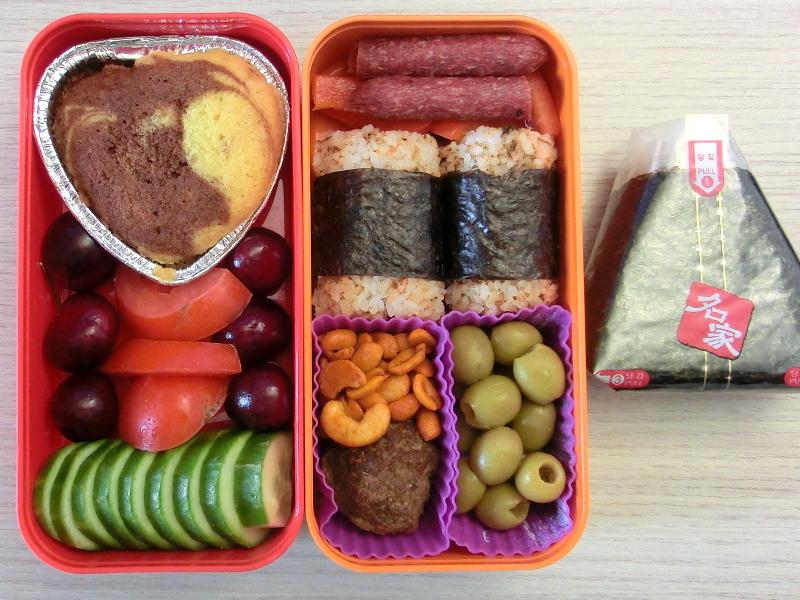 Bento Box gefüllt mit Kuchen, Kirschen, Tomate, Gurke, Salamie, Paprika, Onigiri, Erdnüsse, Hackbällchen, Oliven