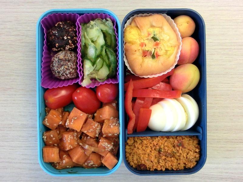 Bento Box gefüllt mit Cous Cous, Paprika, Pfirsich, Quiche, Gurke, Energiebälle, Tomaten, Süßkartoffeln