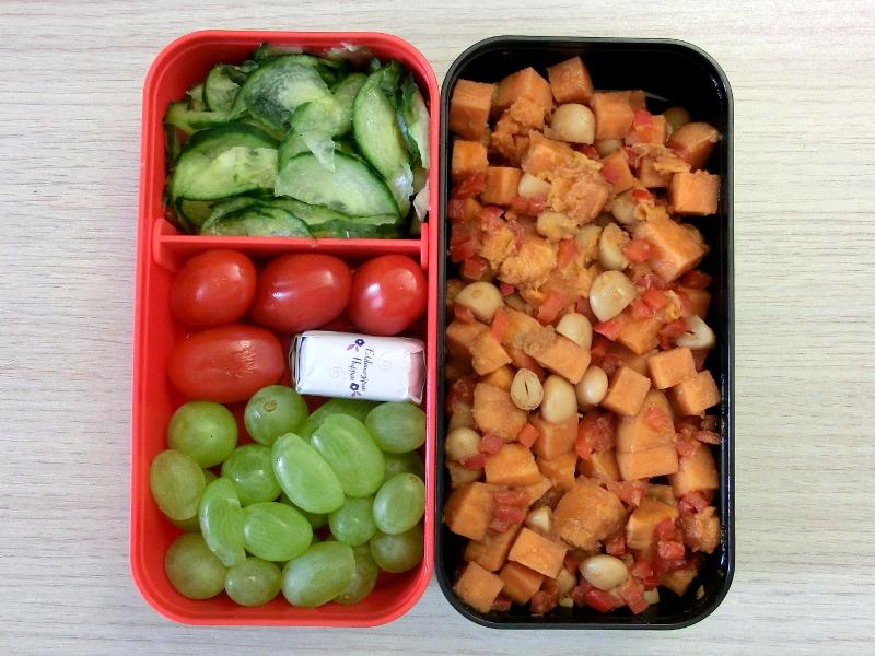 Bento Box gefüllt mit Süßkartoffelsalat, Gurke, Tomaten, Weintrauben, Schokolade
