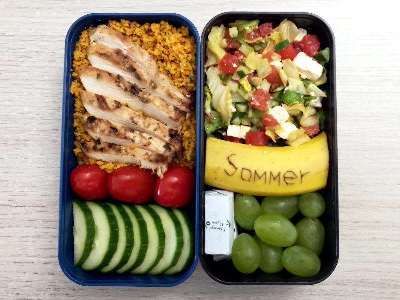 Bento Box gefüllt mit Weintrauben, Schokolade, Banane, Salat mit Schafskäse und Melone, Gurke, Cous Cous, Hähnchen