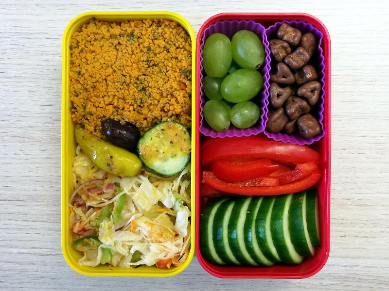 Bento Box gefüllt mit Cous Cous, Salat, Gurke, Paprika, Weintrauben, Schokolade