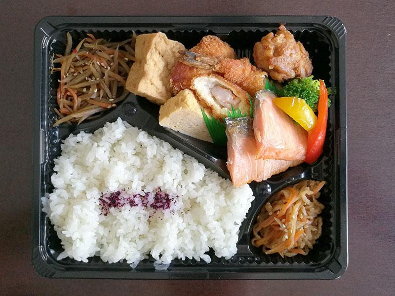 Bento Box gefüllt mit gegrilltem Lachs, frittierter Garnele und frittiertem Hühnchen