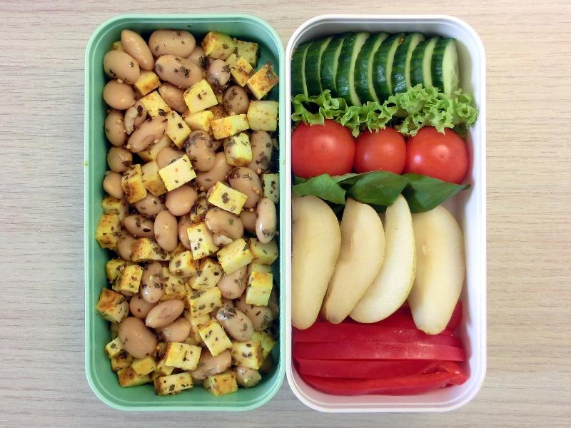 Bento Box gefüllt mit Bohnensalat, Paprika, Birne, Tomate, Gurke