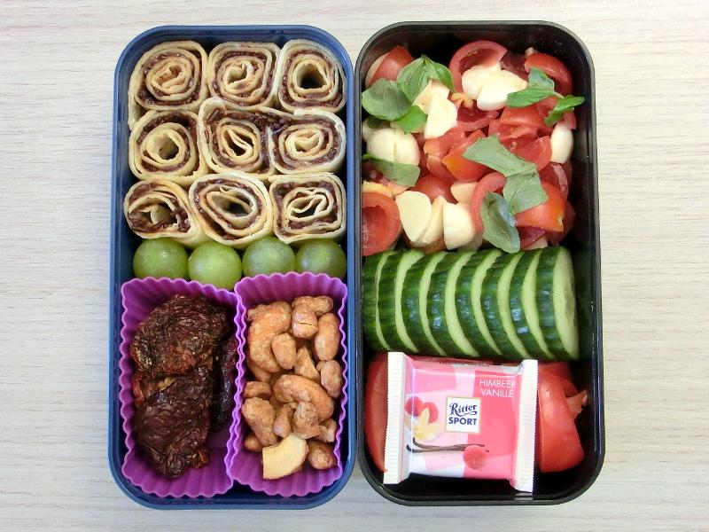 Bento Box gefüllt mit Paprika, Schokolade, Gurke, Tomaten,Morzarella, Wrap, Weintrauben, Getrocknete Tomaten, Erdnüsse