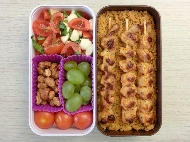 Bento Box gefüllt mit Reis, Hühnchen, Tomaten-Mozarella, Weintrauben, Erdnüssen, Tomaten