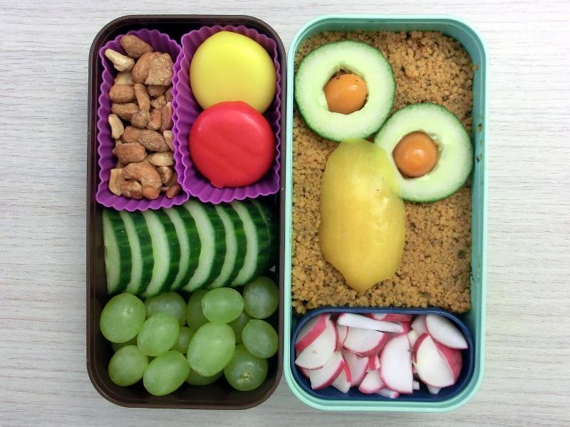 Bento Box gefüllt mit Gurke, Weintrauben, Babybel, Erdnüsse, Cous Cous, Tomaten, Paprika, Radieschen