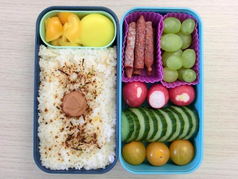 Bento Box gefüllt mit Weintrauben, Salami, Radieschen, Gurke, Tomaten, Reis, Paprika, Babybel