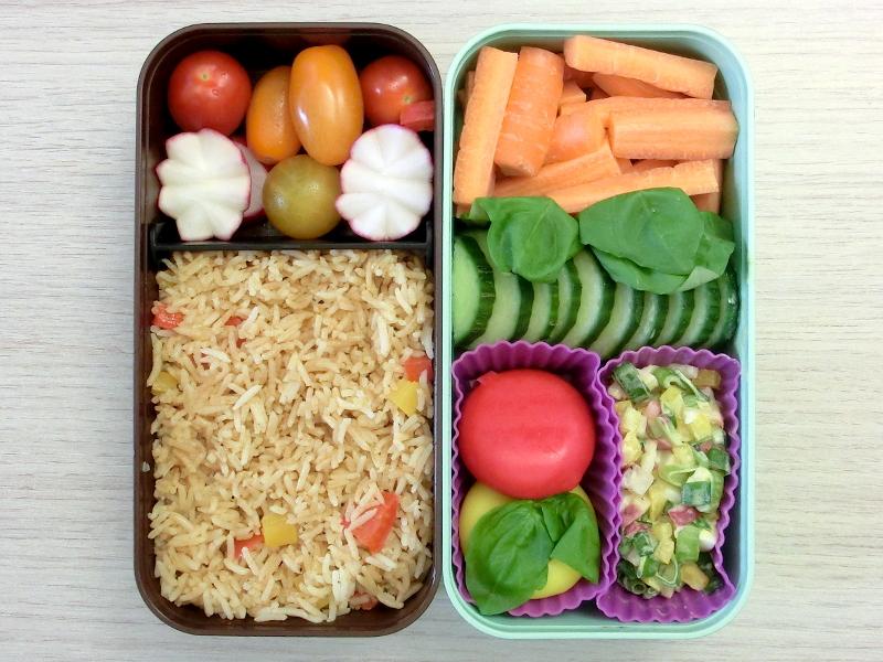 Bento Box gefüllt mit Reis, Radieschen, Tomaten, Möhren, Gurke, Babybel, Kartoffelsalat
