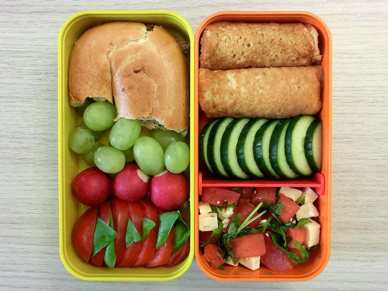 Bento Box gefüllt mit Pancakes, Gurke, Melanoen-Salat, Bagel, Pulled Pork, Weintrauben, Radieschen, Tomate