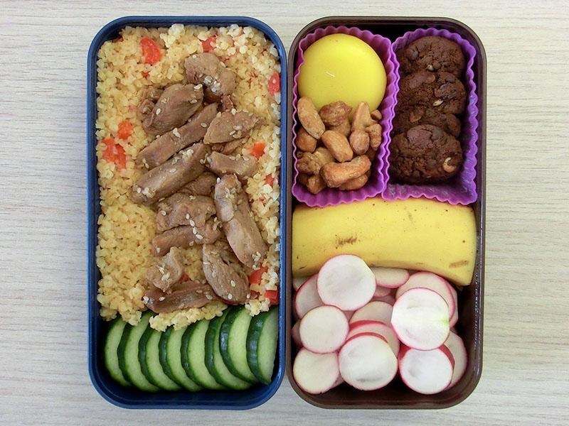 Bento Box gefüllt mit Radieschen, Banane, Kekse, Erdnüsse, Babybel, Bulgur, Hähnchen, Gurke