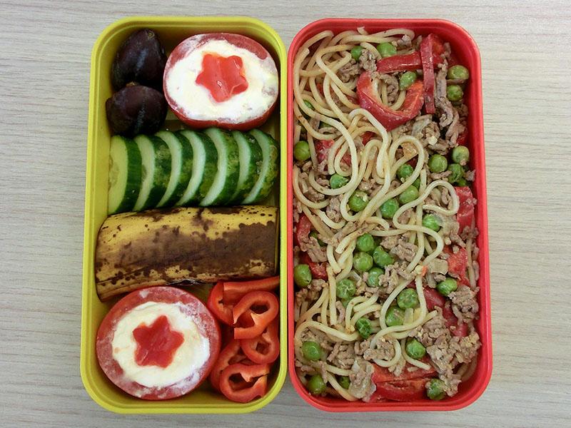 Bento Box gefüllt mit Nudeln mit Hack, Tomate, Gurke, Paprika, Pflaume, Banane