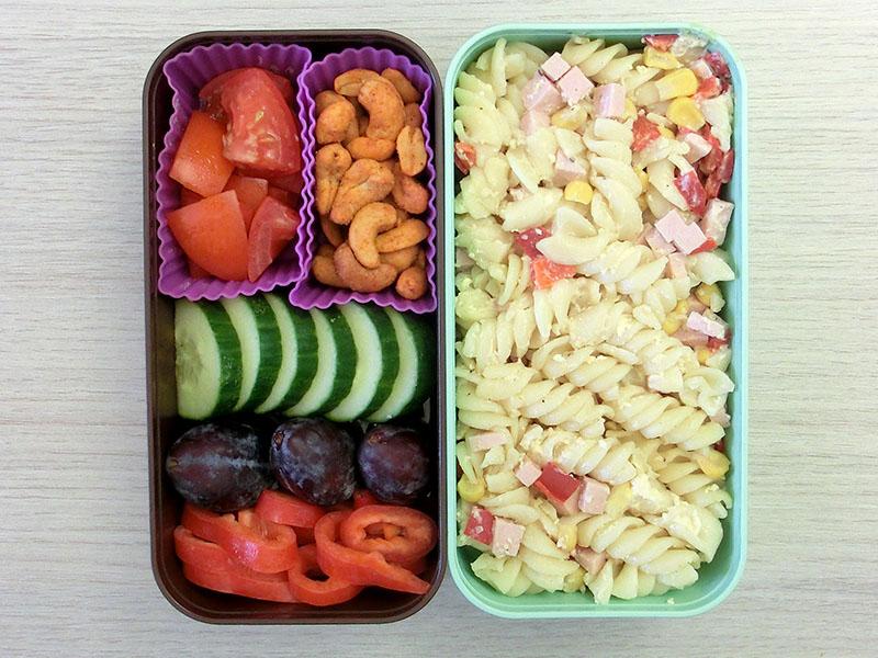 Bento Box gefüllt mit Gurke, Pflaumen, Tomate, Paprika, Erdnüsse, Nudelauflauf