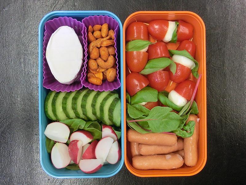 Bento Box gefüllt mit Gurke, Radieschen, Käse, Erdnüsse, Tomaten, Mozzarella, Würstchen