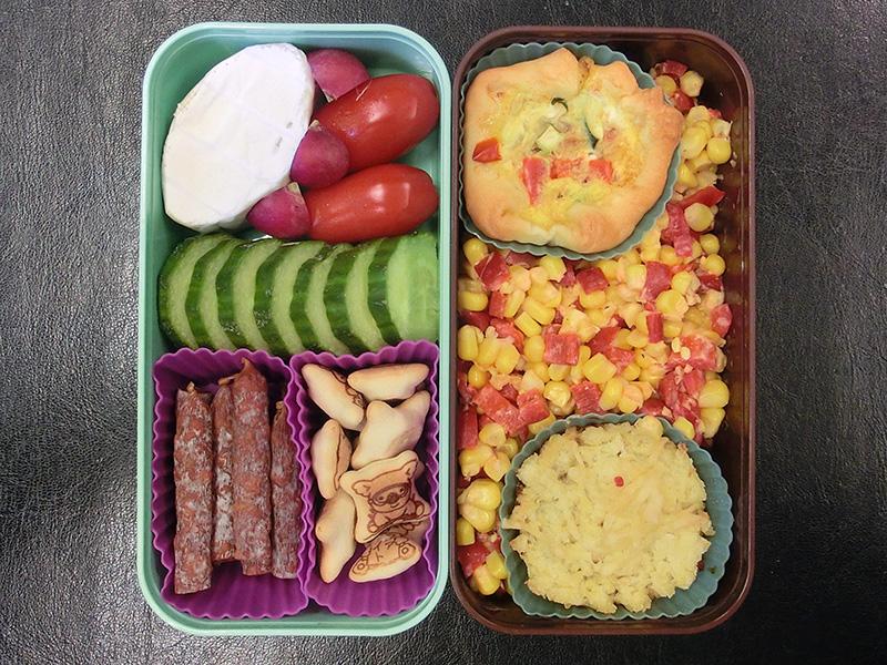 Bento Box gefüllt mit Gurke, Radieschen, Tomaten, Würstchen, Käse, Japanische Koalas, Quiche, Shepards Pie, Mais
