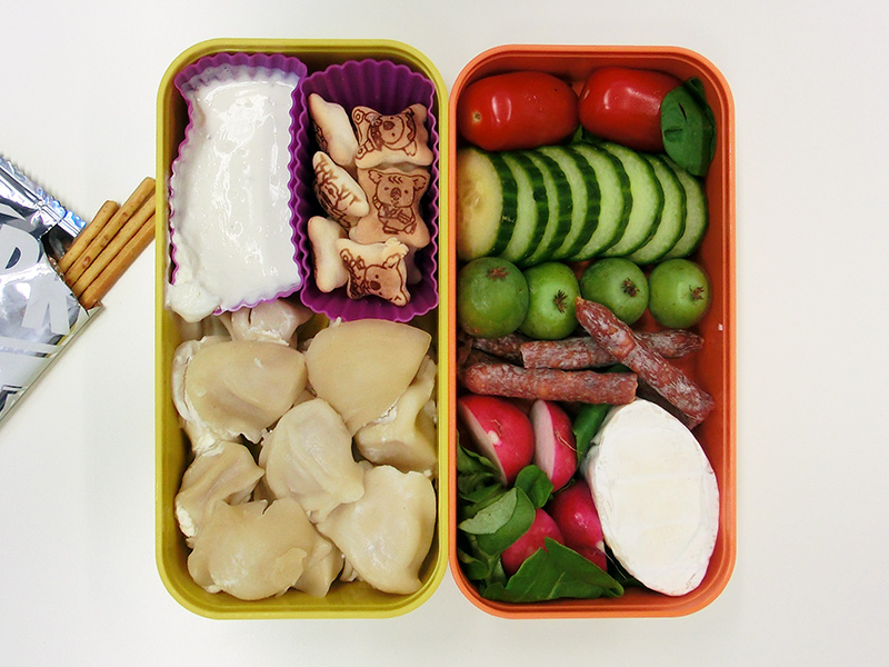 Bento Box gefüllt mit Gurke, Tomaten, Kiwi-Beeren, Salami, Käse, Radieschen, Koalas, Pelmeni, Dipp, Pretzelstangen
