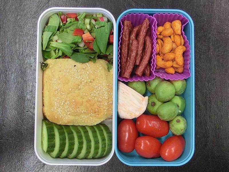 Bento Box gefüllt mit Gurke, Brötchen, Salat, Tomaten, Kiwi-Beeren, Käse, Erdnüsse, Salami