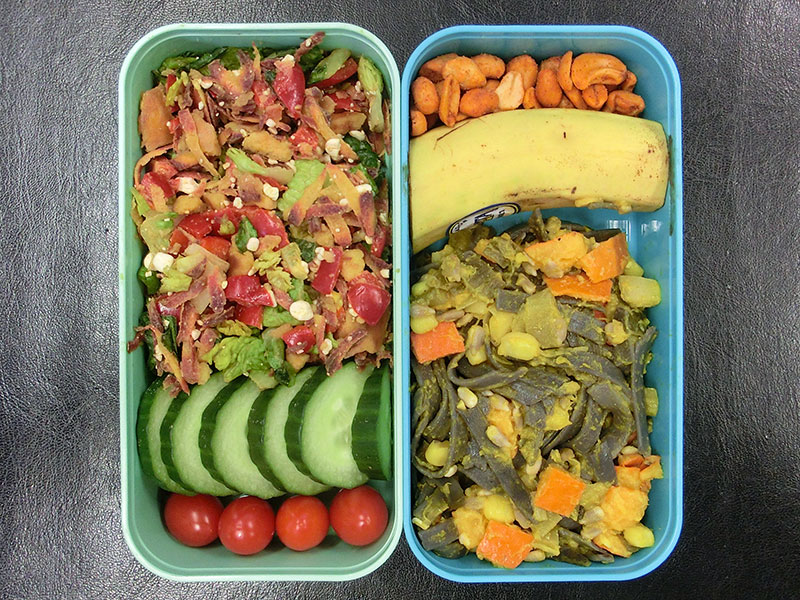Bento Box gefüllt mit Kürbisnudeln, Banane, Erdnüsse, Salat, Gurke, Tomaten