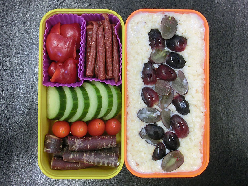Bento Box gefüllt mit Violette Möhren, Tomaten, Gurke, Paprika, Salami, Milchreis, Weintrauben