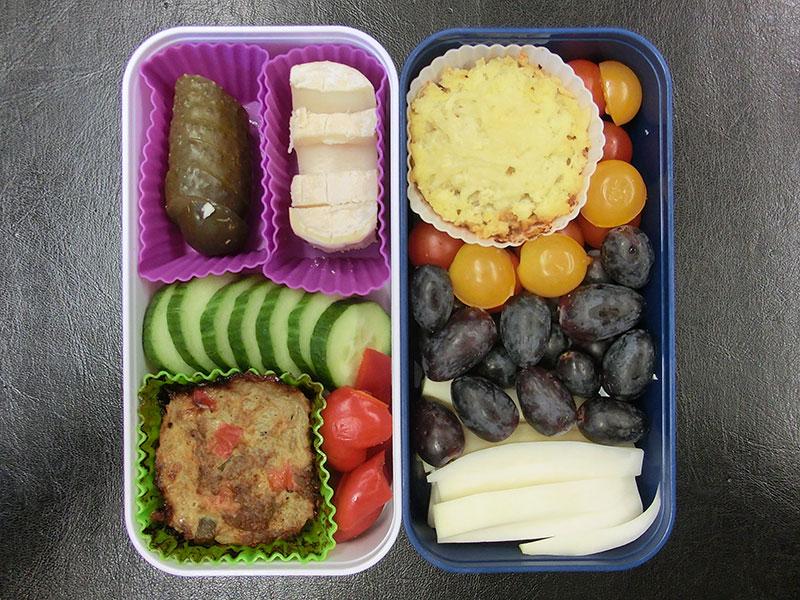 Bento Box gefüllt mit Weintrauben, Tomaten, Kohlrabi, Sheppards Pie, Käse, Gurke, Paprika, Pulled Pork Auflauf