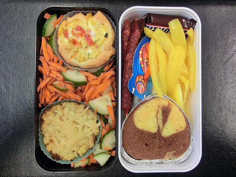 Bento Box gefüllt mit Paprika, Kuchen, Käse, Würstchen, Schokolade, Quiche, Auflauf, Salat