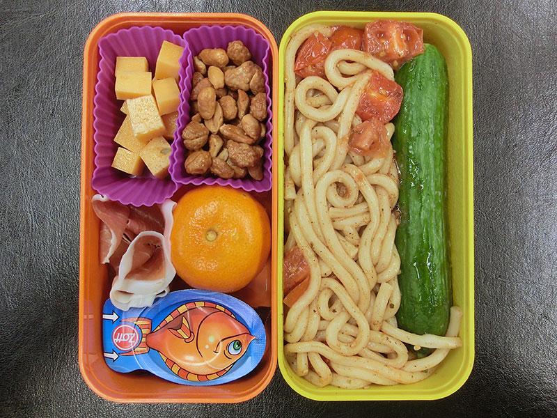 Bento Box gefüllt mit Nudeln, Gurke, Erdnüsse, Käse, Mandarine, Schinken, Käse, Schokolade