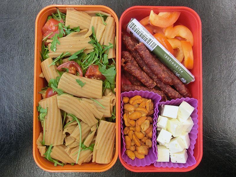 Bento Box gefüllt mit Nudelsalat, Paprika, Würstchen, Paleoriegel, Käse, Erdnüsse