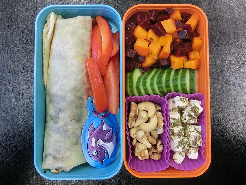 Bento Box gefüllt mit Kürbis, Rote Beete, Nüsse, Gurke, Schafskäse, Bananenwrap, Paprika, Käse