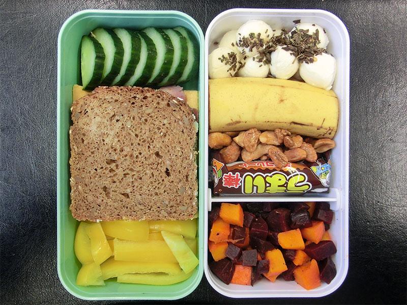 Bento Box gefüllt mit Erdnüsse, Banane, Kürbis-Rote Beete Salat, Paprika, Mozzarella, Gurke, Brot