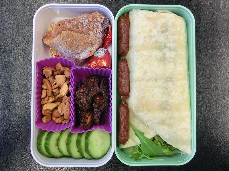 Bento Box gefüllt mit Wrap, Salami, Schneeballen, Schokolade, Erdnüsse, Getrocknete Tomaten, Gurke