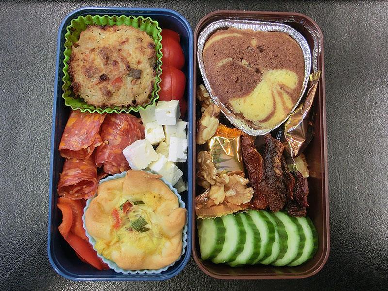 Bento Box gefüllt mit Gurke, Schokolade, Getrocknete Tomaten, Kuchen, Hackauflauf, Paprika, Schafskäse, Salami, Quiche