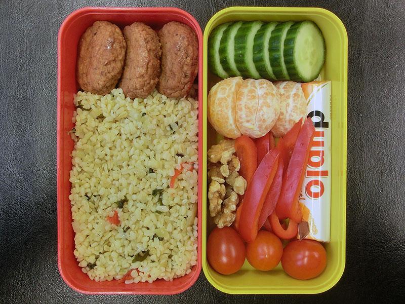 Bento Box gefüllt mit Bulgur, Frikadellen, Tomaten, Paprika, Schokolade, Walnüsse, Mandarine, Gurke
