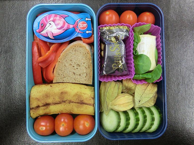 Bento Box gefüllt mit Käse, Paprika, Brot, Banane, Tomaten, Schokolade, Ziegenkäse, Pysalis, Gurke