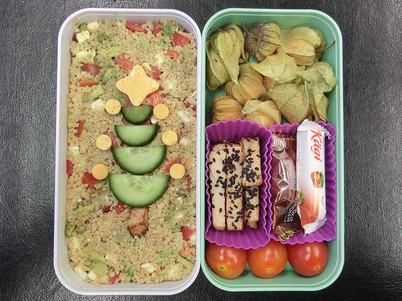Bento Box gefüllt mit Cous cous, Käse, Gurke, Hühnchen, Schokolade, Tomaten, Physalis